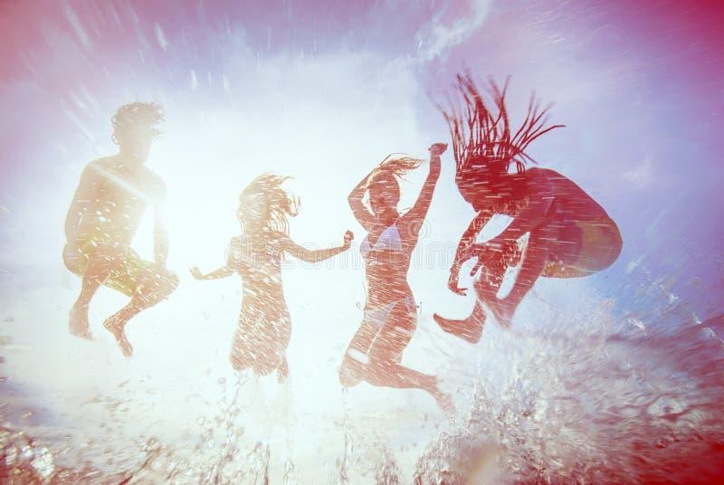 De zomersilhouetten van gelukkige jongeren die in overzees op B springen royalty-vrije stock afbeelding
