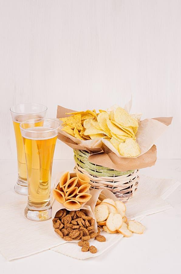 De zomersnacks en lagerbierbier in glas - nachos, croutons, spaanders, tortilla in rustieke mand en document hoeken op wit hout b stock afbeelding