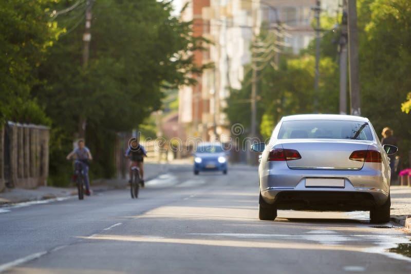 De zomerstad met twee jonge jongens die fietsen langs de straat berijden stock foto's