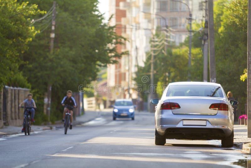 De zomerstad met twee jonge jongens die fietsen langs de straat berijden royalty-vrije stock afbeeldingen