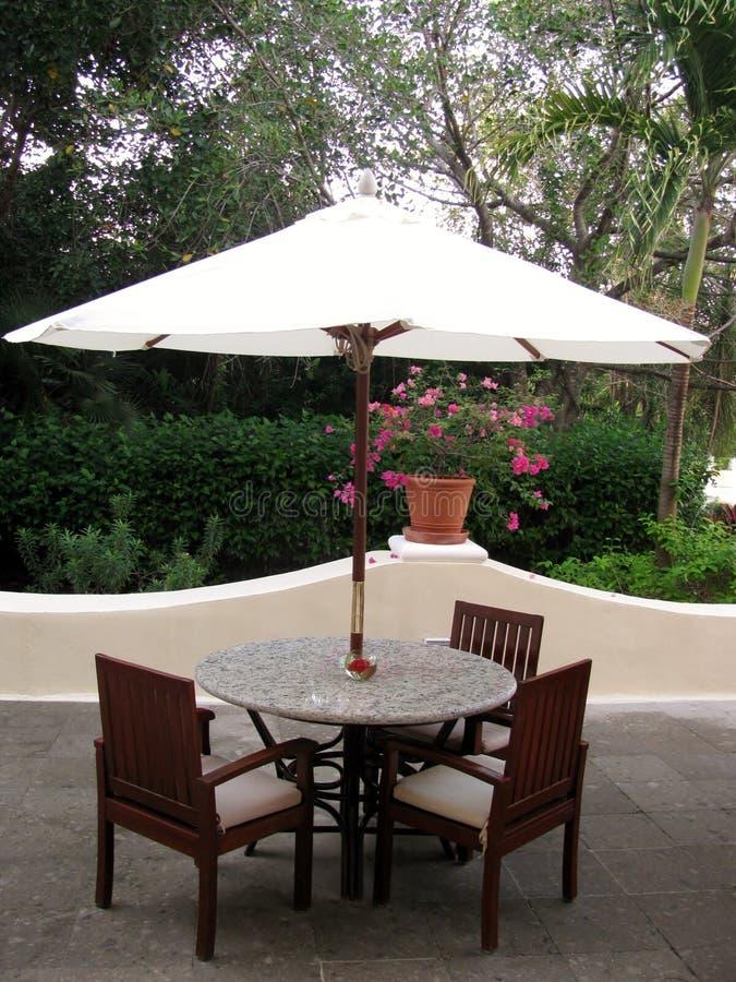 De zomerterras met lijsten en houten stoelen onder paraplu stock afbeelding