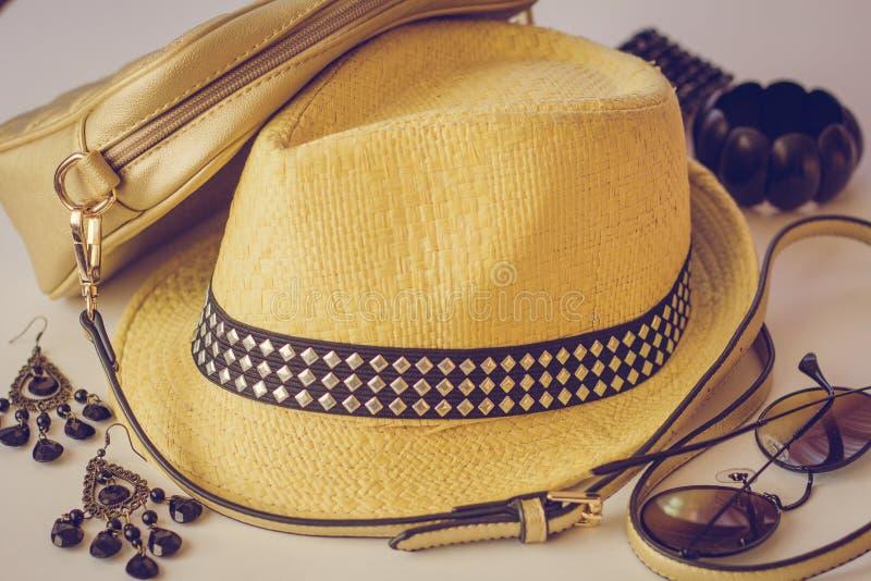 De de zomertoebehoren, een zak, een strohoed, de zonnebril en de oorringen liggen op de lijst, close-up stock afbeeldingen