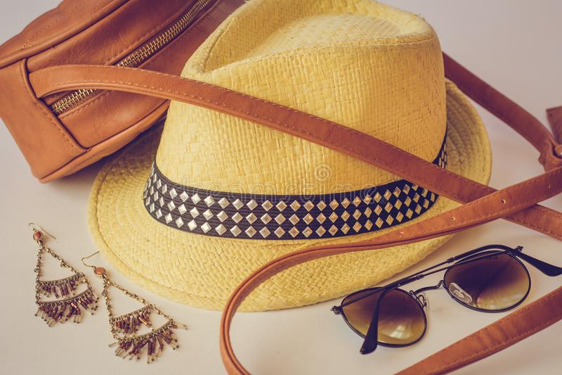 De de zomertoebehoren, een zak, een strohoed, de zonnebril en de oorringen liggen op de lijst Vier toebehoren van beige kleur royalty-vrije stock fotografie