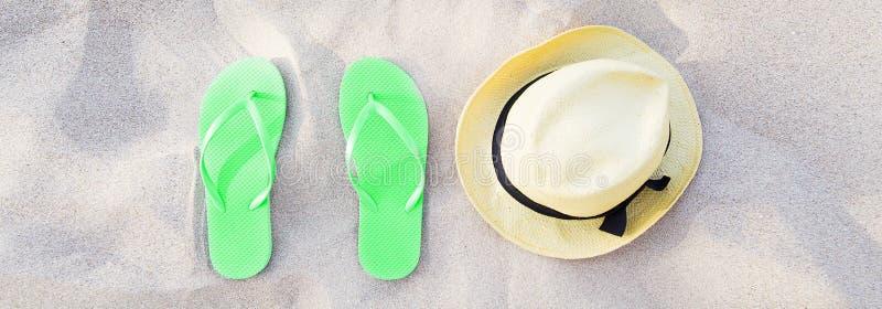 De zomertoebehoren op de bannerachtergrond van de strandtextuur Groene Wipschakelaars en hoed op zand hoogste mening Pantoffelssc stock afbeelding
