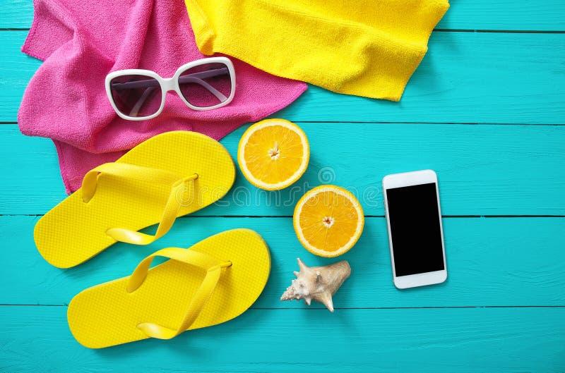 De zomertoebehoren op blauwe houten achtergrond Gele wipschakelaars, handdoeken, zonnebril, mobiele telefoon en sinaasappelen De  royalty-vrije stock foto's