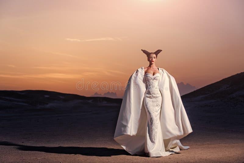 De zomervakantie en vakantie Bruid in zandduinen op berglandschap royalty-vrije stock afbeeldingen