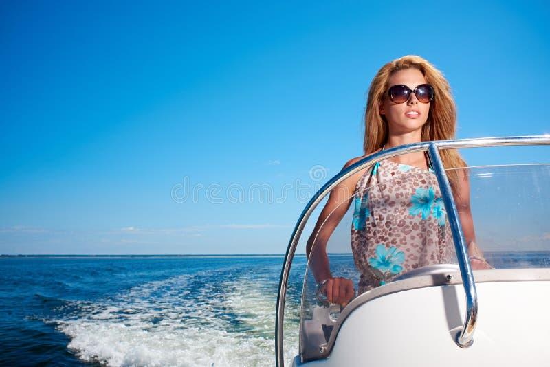 De zomervakantie - meisje die een motorboot drijven stock foto
