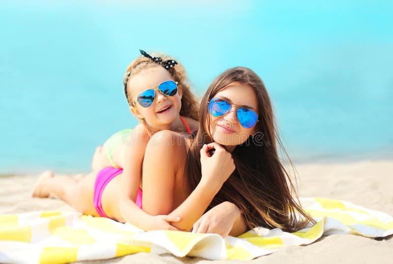 De zomervakantie, ontspanning, reis - moeder en kind liggen die op strand rusten stock afbeeldingen