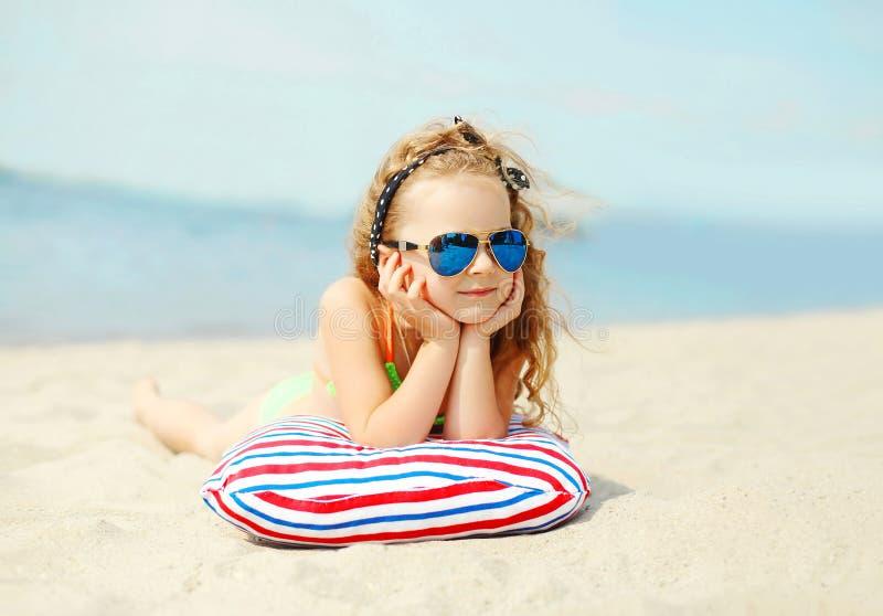 De zomervakantie, ontspanning, reisconcept - portretkind liggen die op strand rusten royalty-vrije stock fotografie
