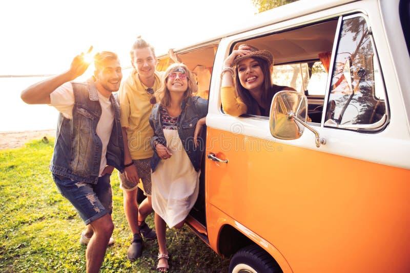 De zomervakantie, wegreis, vakantie, reis en mensenconcept - glimlachende jonge hippievrienden die pret over minivan hebben stock afbeelding