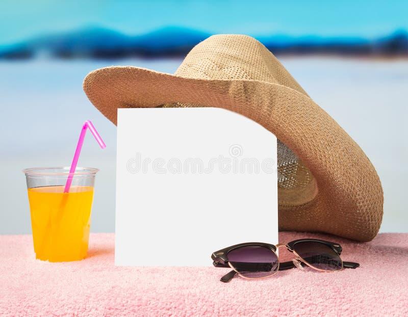 De zomerverkoop of aanbiedingsachtergrond voor reclame Witte vierkante kaart op handdoek met zonnebril, gele cocktail en hoed royalty-vrije stock foto's