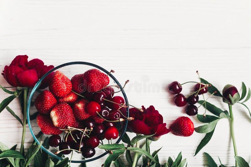 De de zomervlakte lag verse kersen en aardbeien in modieuze glas stock foto's