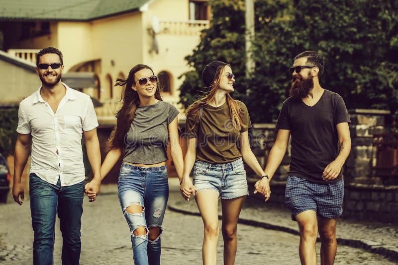 De zomervrije tijd van gelukkige, glimlachende vrienden die langs baksteenweg lopen royalty-vrije stock foto