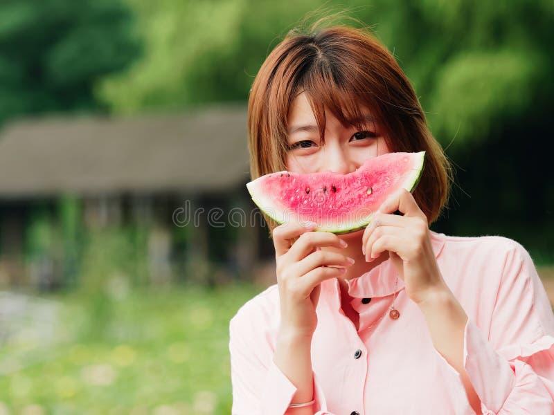 De zomervrouw die watermeloenplak eten Glimlachend Chinees meisje die watermeloen in park eten Vakantielevensstijl De donkerbruin stock afbeelding
