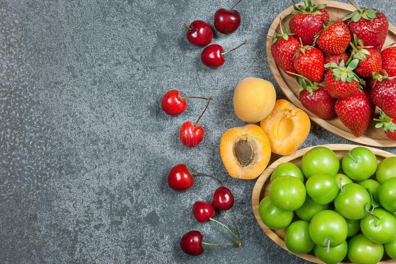 De zomervruchten, groene pruim, rode kers, aardbei, abrikoos op grijze rustieke achtergrond royalty-vrije stock afbeeldingen