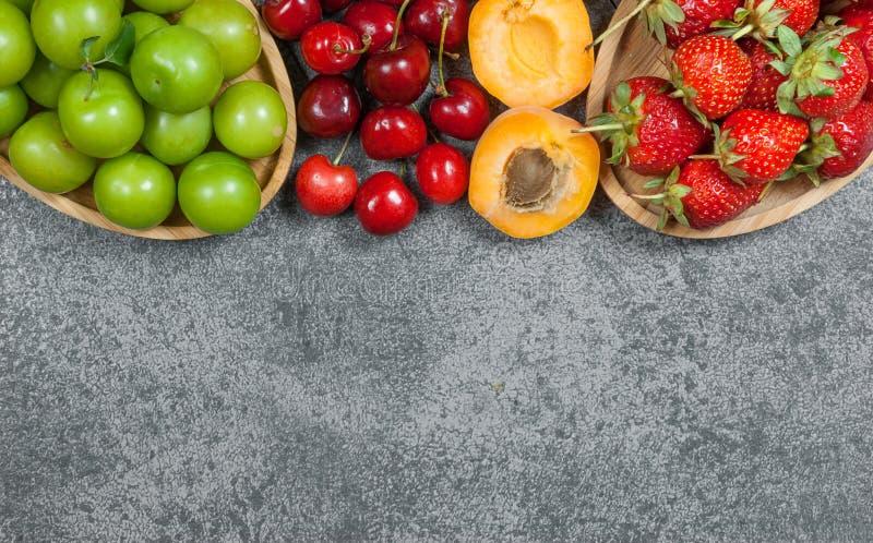De zomervruchten, groene pruim, rode kers, aardbei, abrikoos op grijze rustieke achtergrond stock afbeeldingen