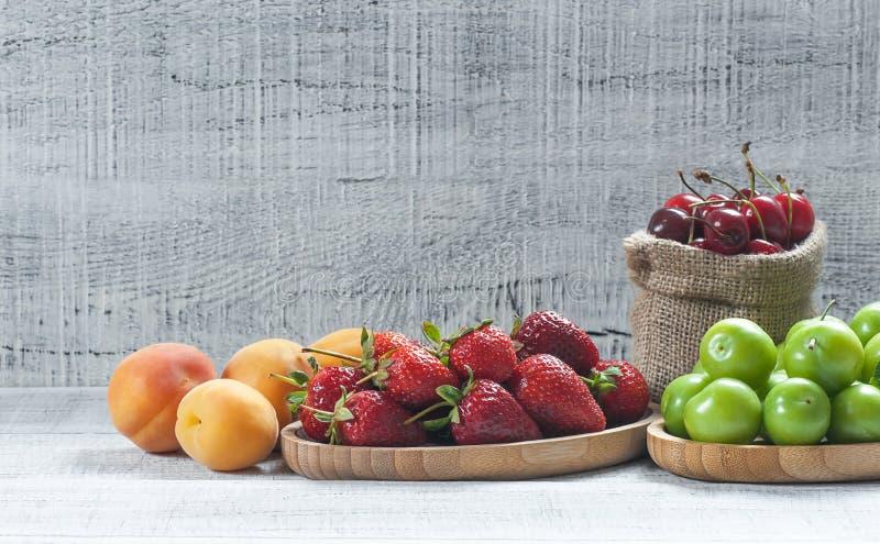 De zomervruchten, groene pruim, rode kers, aardbei, abrikoos op witte houten achtergrond royalty-vrije stock foto