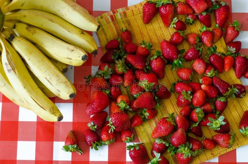 De zomervruchten van markt, heel wat rijpe aardbeien en grote bos van gele bananen royalty-vrije stock foto