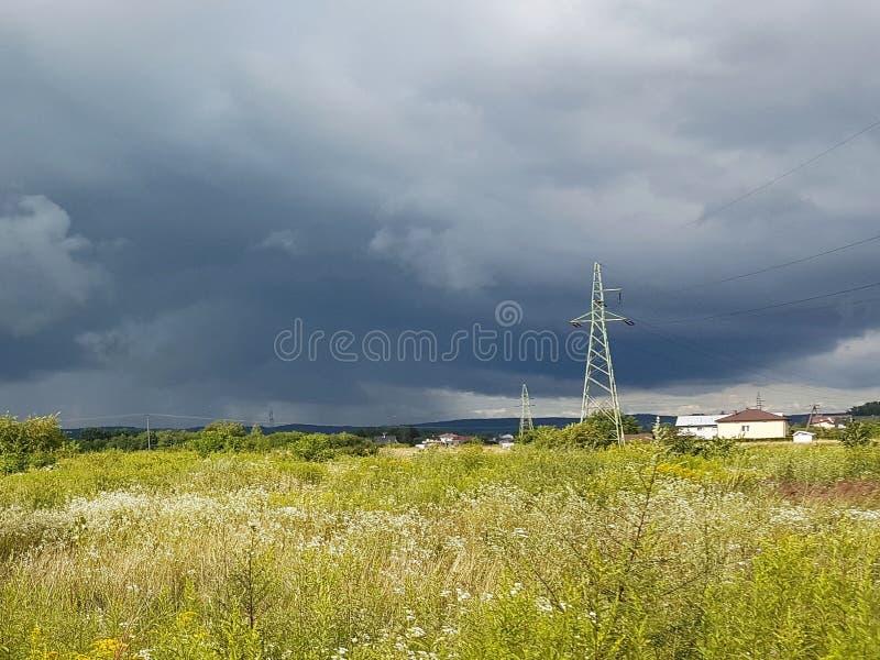 De zomerweide in de stralen van de zon met een dreigende onweerswolk en elektriciteitslijn Weerverandering Onweer op een zonnige  royalty-vrije stock fotografie