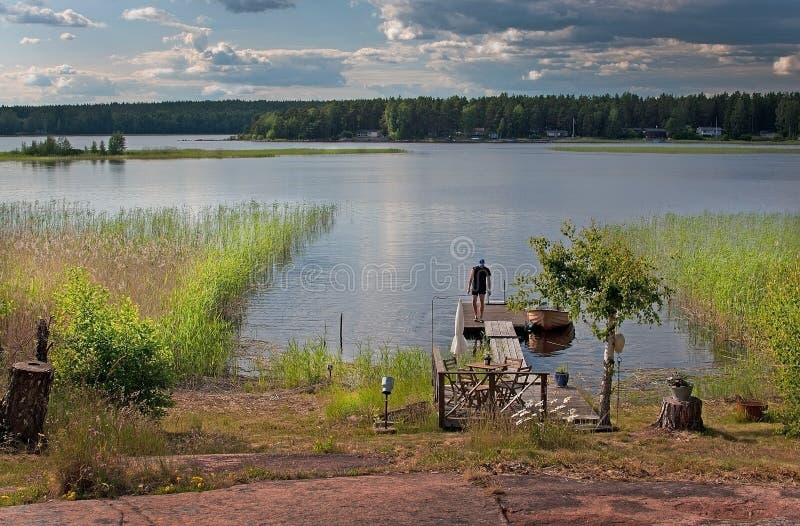De zomerzonsondergang door het meer in Varmland stock foto's
