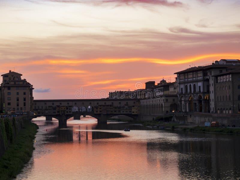 De zomerzonsondergang over Arno River en Ponte Vecchio in Florence, Italië stock foto