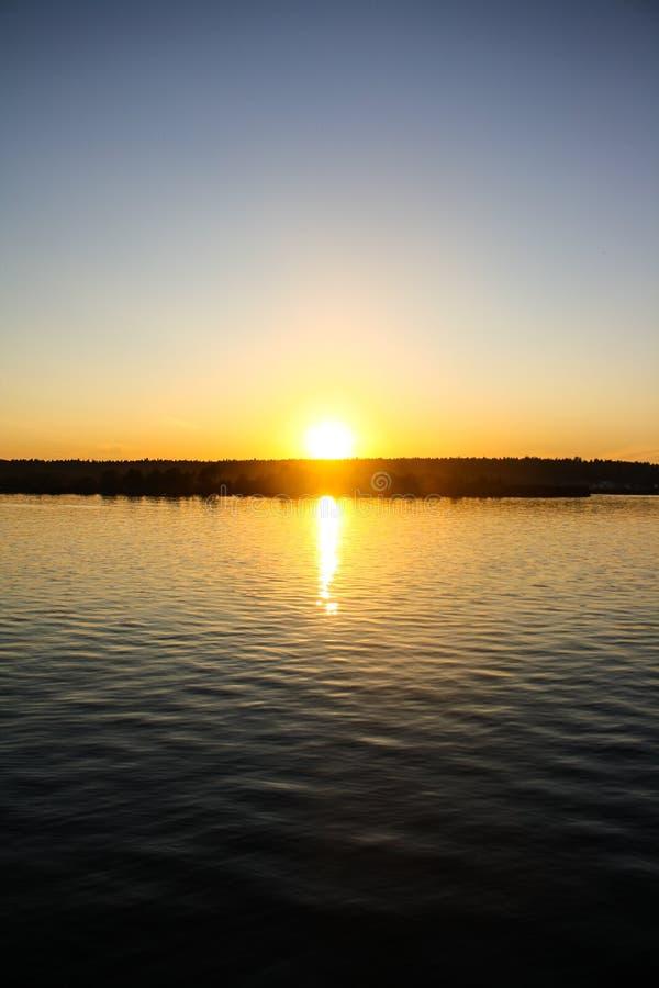 De zomerzonsondergang over de rivier vector illustratie