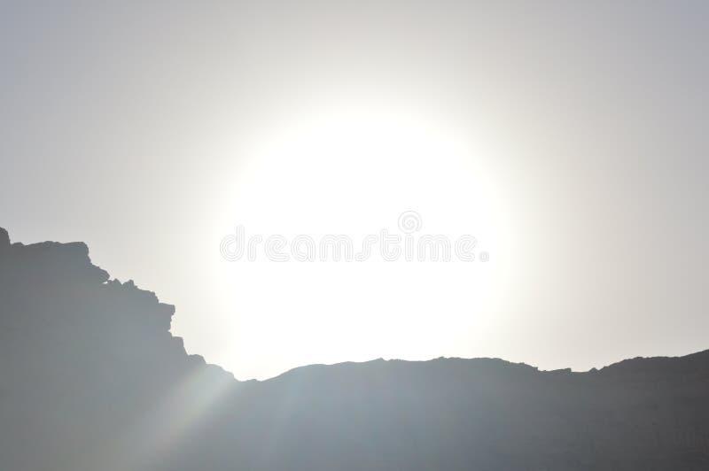 De zon achter de berg stock foto's