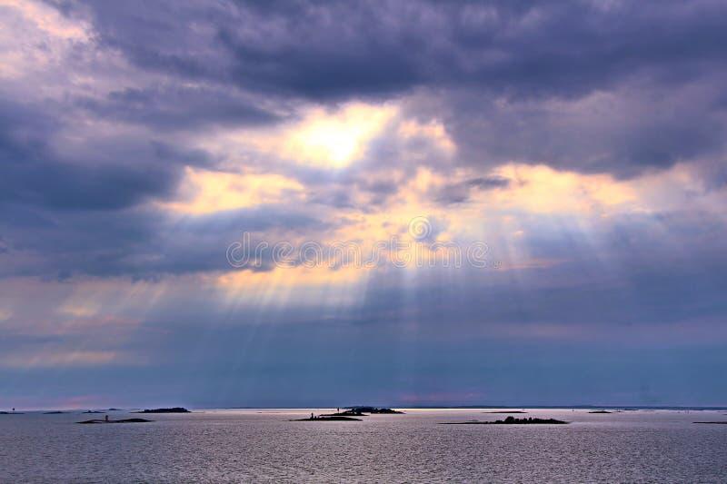 De zon achter de wolken met stralen die van licht neer op overzees glanzen royalty-vrije stock afbeeldingen