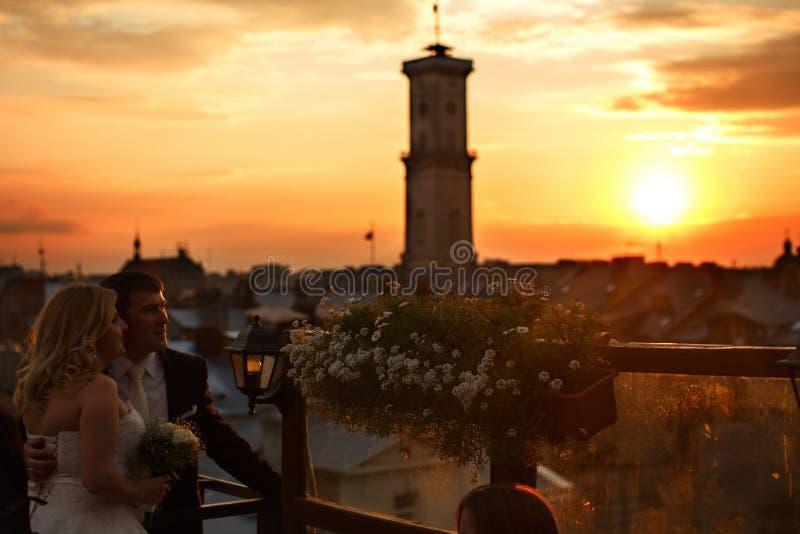 De zon declinging over een oude stad terwijl bruid en bruidegom tal stock afbeeldingen