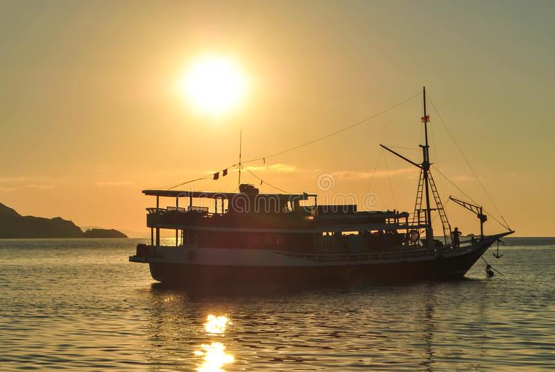 De zon die achter een zeilboot bij een kalme ankerplaats in tropisch Komodo-eiland, Labuan Bajo, Fores, Indonesië plaatsen royalty-vrije stock foto's