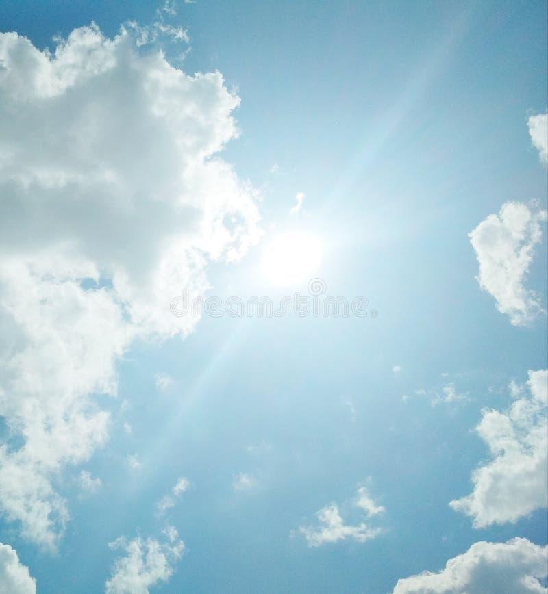 De zon die helder in de bewolkte blauwe hemel glanzen stock afbeelding