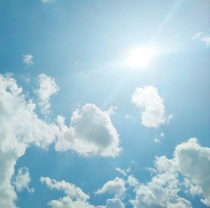 De zon die helder in de bewolkte blauwe hemel glanzen stock afbeeldingen