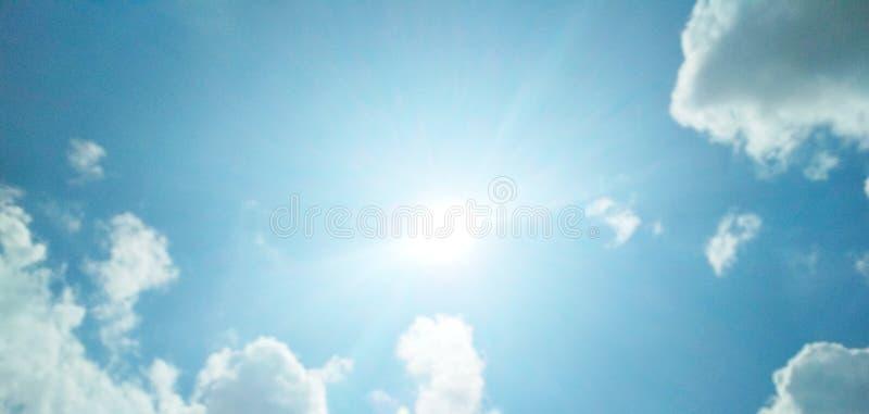 De zon die helder in de bewolkte blauwe hemel glanzen stock foto