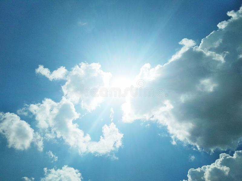 De zon die helder in de bewolkte blauwe hemel glanzen stock foto's