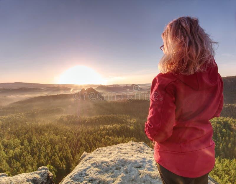 De Zon die van het meisjeshorloge bij horizon toeneemt Kleurrijke de lentevallei stock afbeeldingen