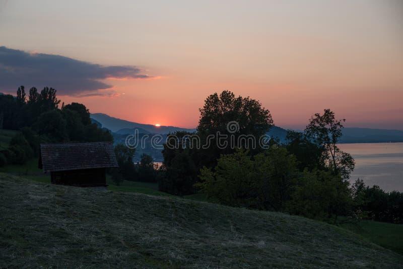 De zon gaat onderaan over meerthunersee en heuvelig landschap stock foto's
