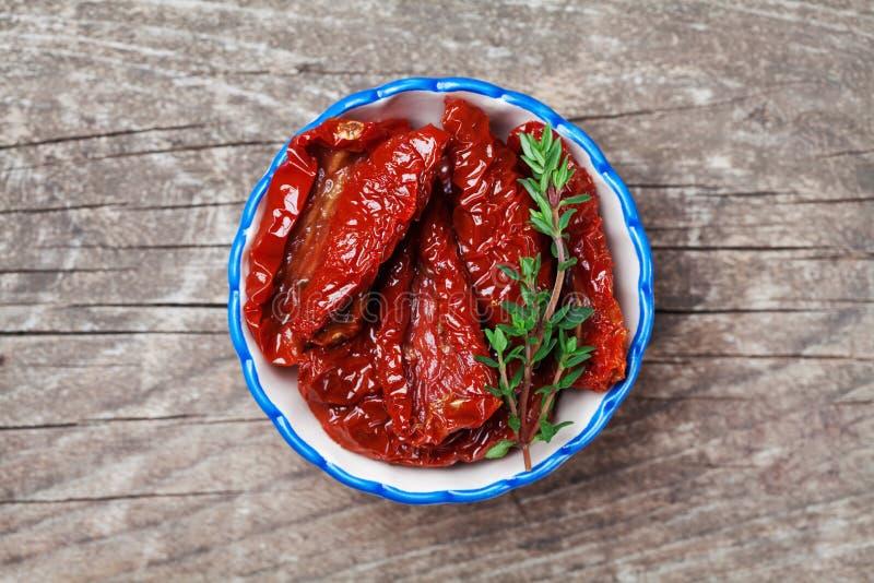 In de zon gedroogde tomaten in kom op rustieke houten achtergrond Hoogste mening stock foto's