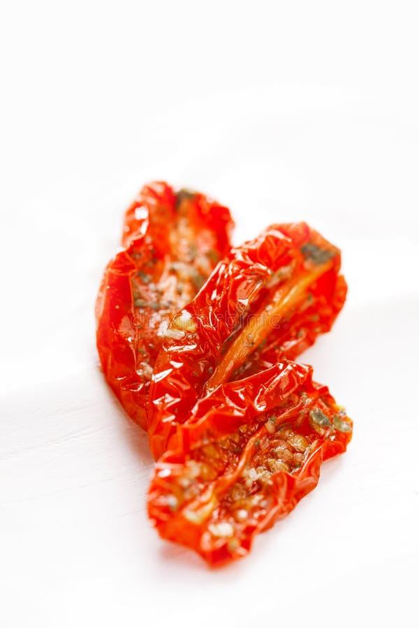In de zon gedroogde tomaten met olijfolie in een oud wit hout stock fotografie