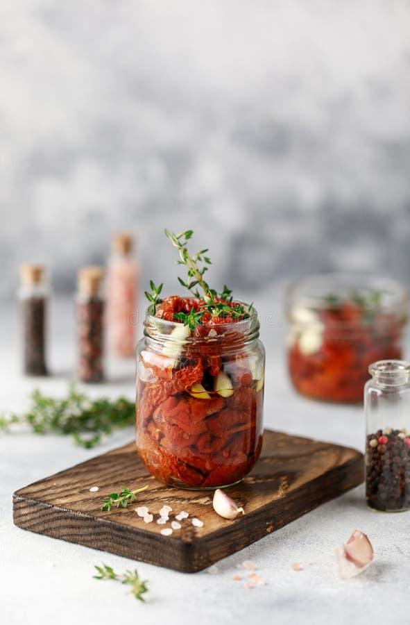 In de zon gedroogde tomaten met verse kruiden en kruiden, overzees zout in olijfolie in een glaskruik Hoogste mening Druk voor ke royalty-vrije stock foto's