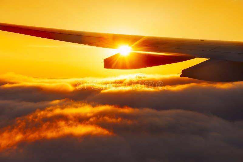 De zon glanst door de vleugel van het vliegtuig boven de wolken tijdens de vlucht bij zonsondergang De atmosfeer van reis en vaka stock afbeeldingen
