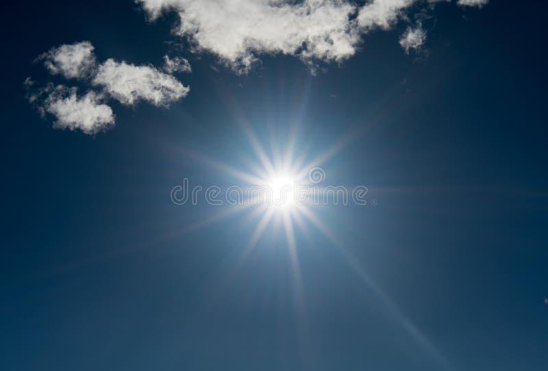 De zon glanst helder in een stervorm in de brigh blauwe hemel met een paar witte horizontale wolkenachtergrond stock fotografie