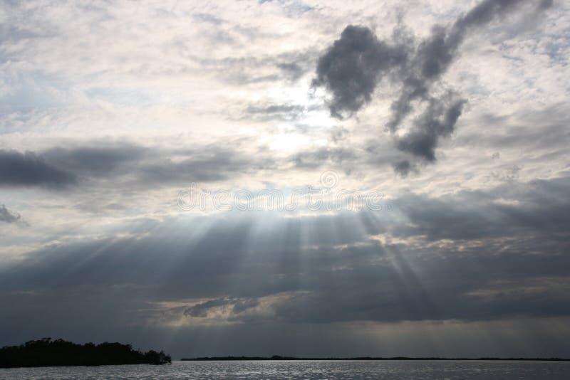 De zon komt trought de wolken op de oceaan royalty-vrije stock fotografie