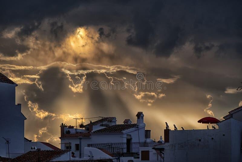 De zon laat vallen als zonnestralenonderbreking door wolk, over het dorp van Sedella, neer Spanje stock fotografie