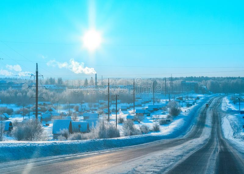 De zon over de de winter bosweg in de ijzige ochtend stock afbeeldingen