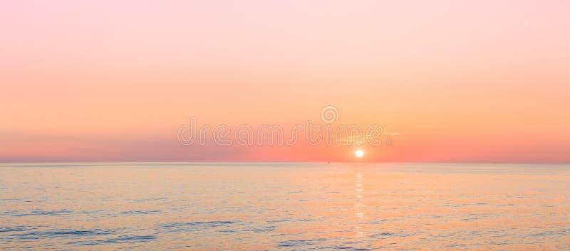 De zon plaatst op Horizon bij Zonsondergangzonsopgang over Overzees of Oceaan stock fotografie