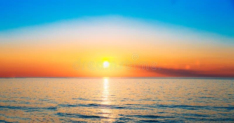 De zon plaatst op Horizon bij Zonsondergangzonsopgang over Overzees of Oceaan T stock foto