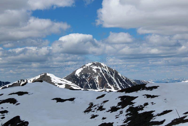 De zon raakt de sneeuwpiek van de bergen van Altay stock afbeelding
