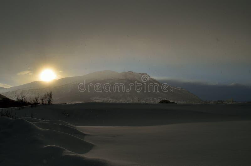 De zon tussen wolken over sneeuwberg als sneeuw valt neer royalty-vrije stock foto