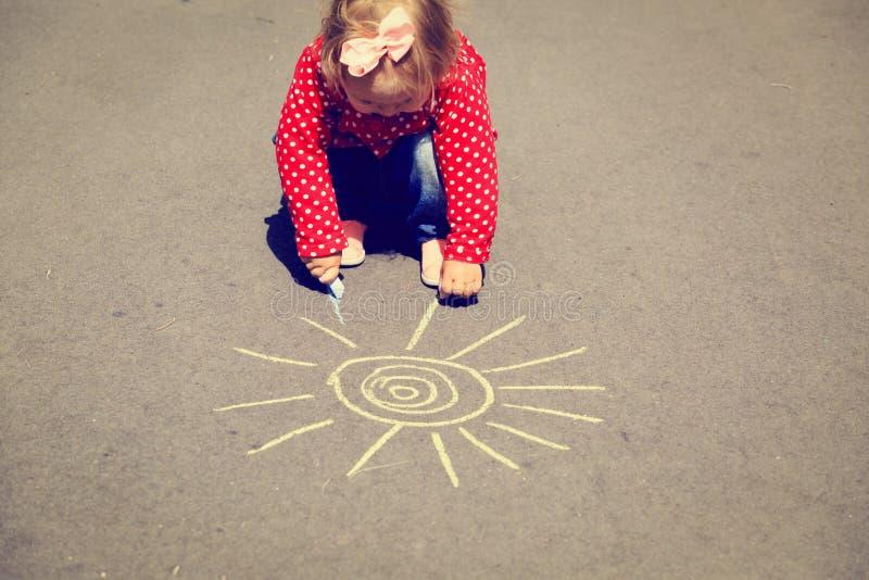 De zon van de meisjetekening op asfalt in openlucht stock afbeelding