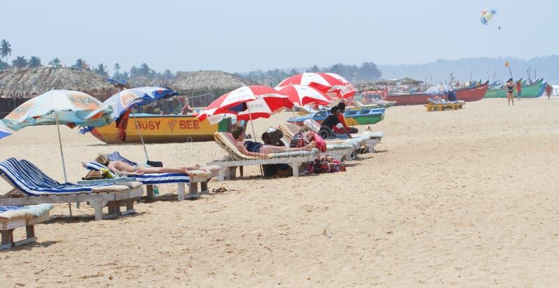 De zon van toeristen het baden op een strand van Goa, India royalty-vrije stock foto